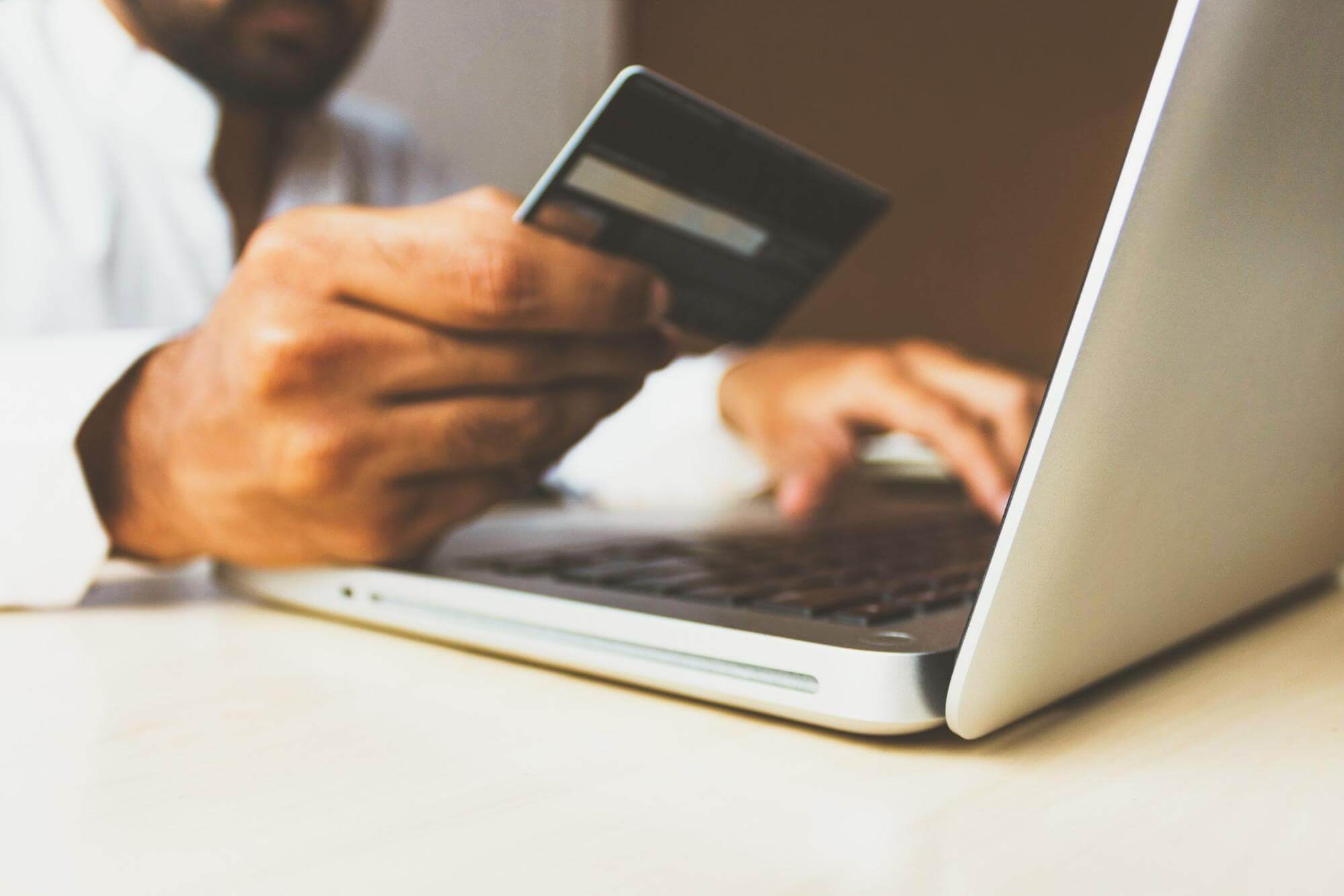 man online shopping holding a bank card