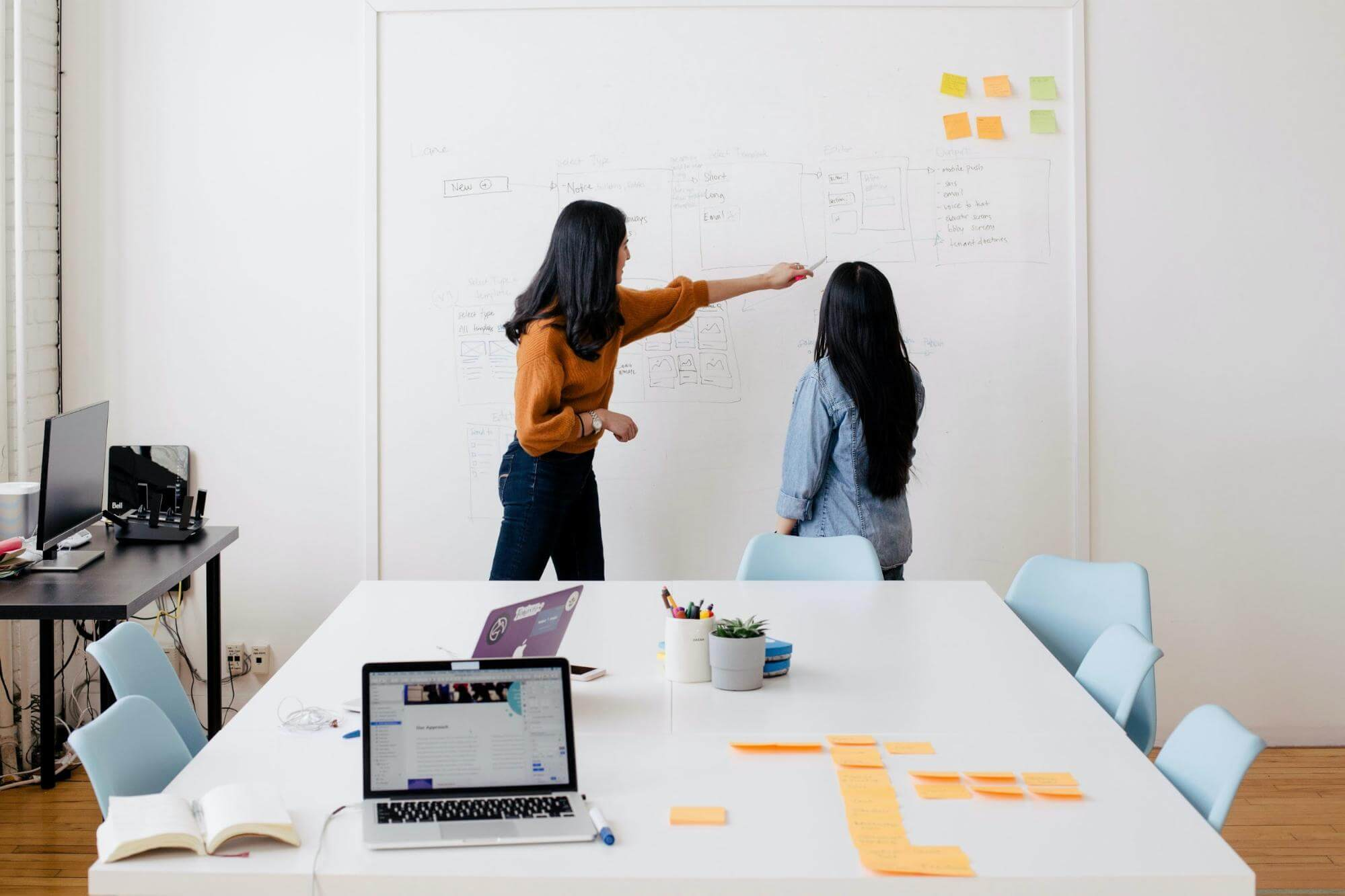 understanding your client in a meeting room pointing at a whiteboard